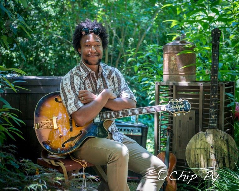 Portrait of Artists Brian Farrow holding his bass guitar while sitting outdoors in the shade