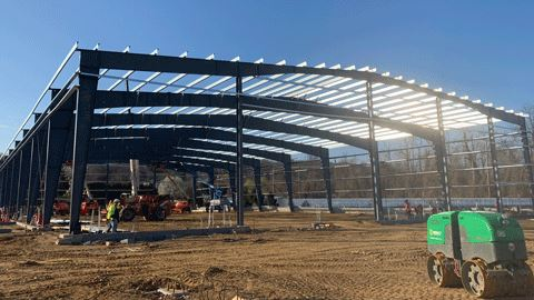A construction site with a large metal structure of new ice rink facility.