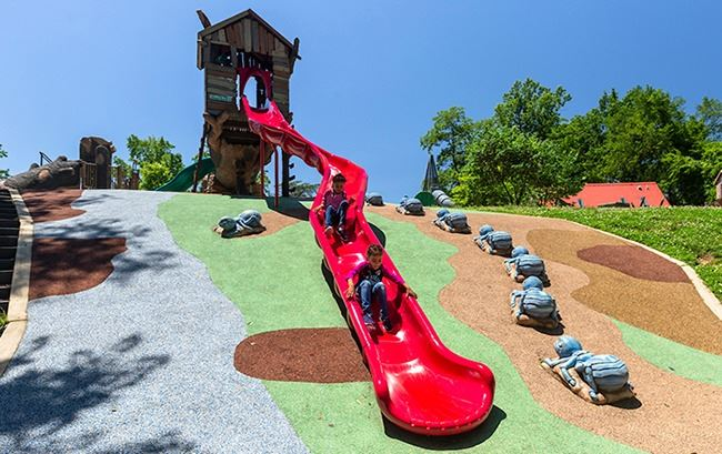 The playground structure with kids sliding down the bright red slide at Walker Mill Regional Park on